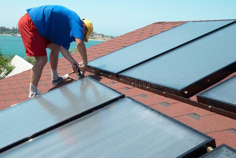 El trabajador instala los paneles solares fotos de archivo