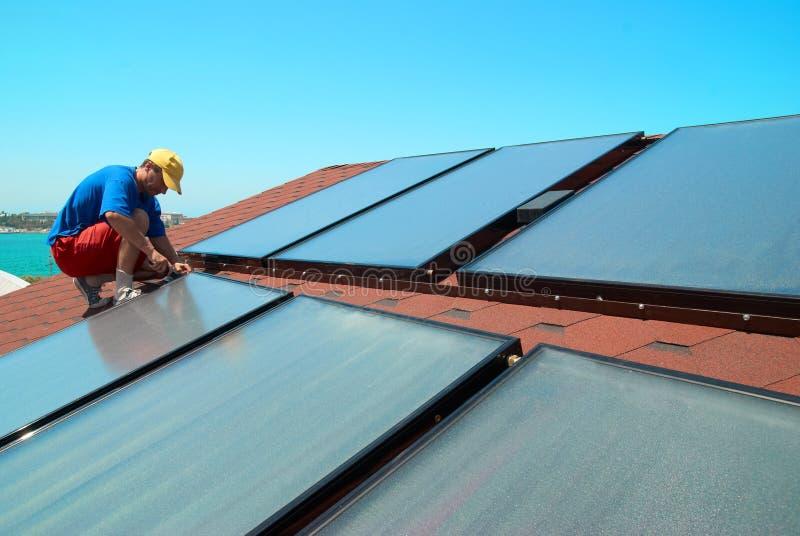 El trabajador instala los paneles solares imagen de archivo libre de regalías