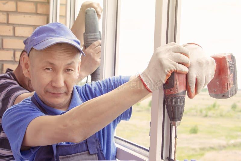El trabajador instala el marco principal del sverdit de la ventana para atar para basar la reparaci?n en edificio alto fotos de archivo