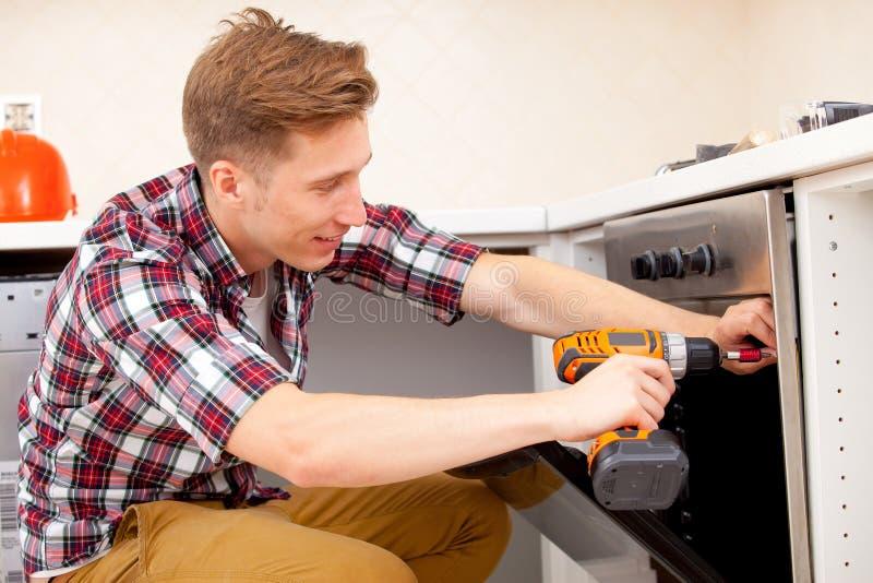 El trabajador instala una cocina eléctrica imagen de archivo