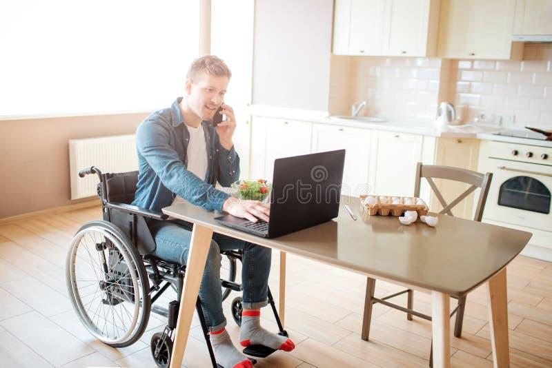 El trabajador joven con incapacidad y las necesidades especiales se sientan en la tabla y el trabajo ?l utiliza el ordenador port imagen de archivo libre de regalías