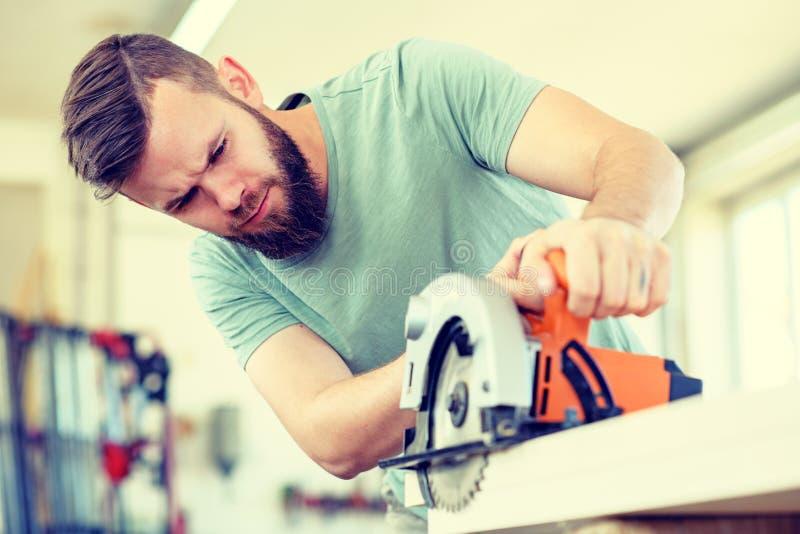 El trabajador joven en un taller de los carpinteros con la mano vio imagen de archivo