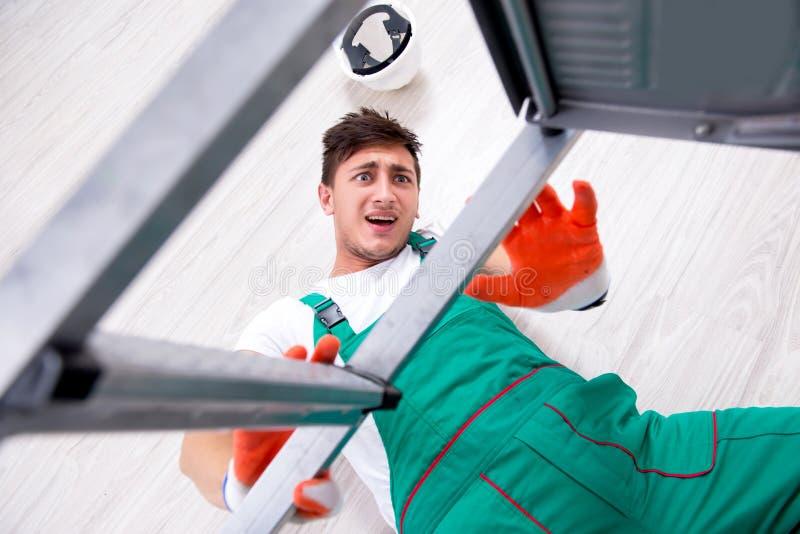 El trabajador joven que cae de la escalera imagen de archivo