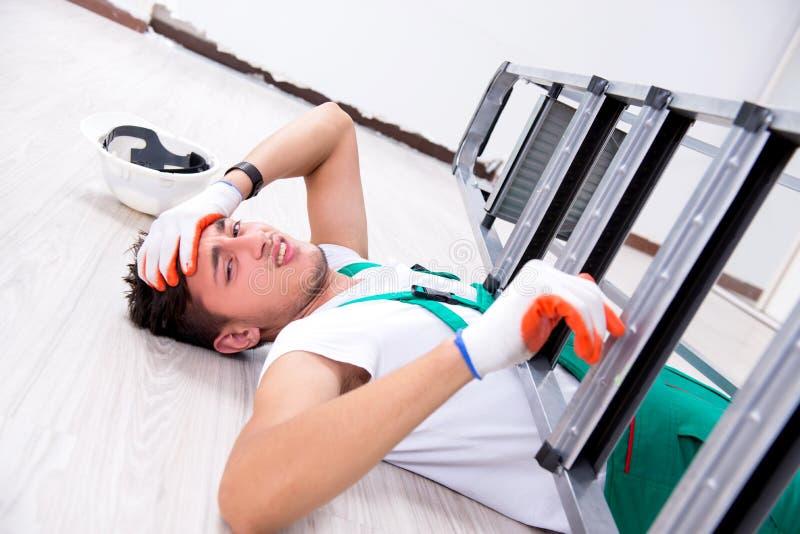 El trabajador joven que cae de la escalera fotos de archivo