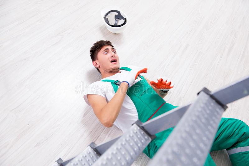 El trabajador joven que cae de la escalera imágenes de archivo libres de regalías