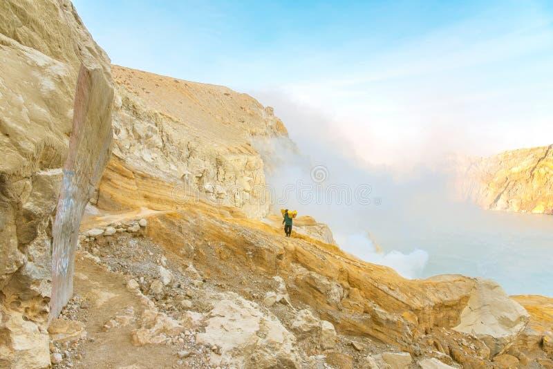 El trabajador lleva el azufre dentro en el volcán de Ijen foto de archivo
