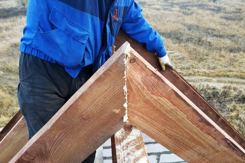 El trabajador mata al clavo en los vigas encima del tejado de la casa imagenes de archivo