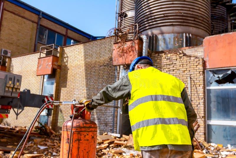 El trabajador mayor está substituyendo los cilindros de gas para el equipo de la soldadura oxiacetilénica a cortar la chatarra po fotografía de archivo libre de regalías