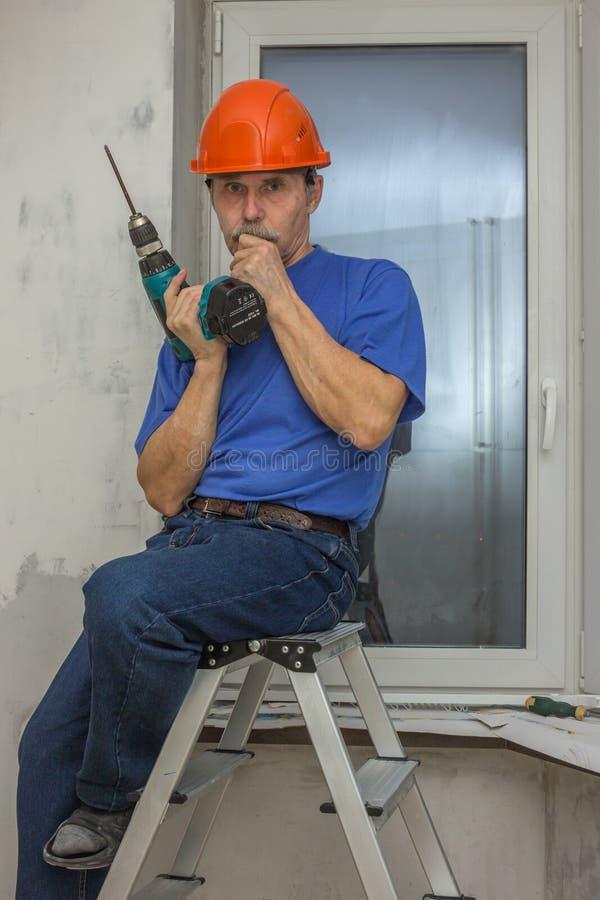 El trabajador mayor se sienta en una pérdida en una escalera fotografía de archivo