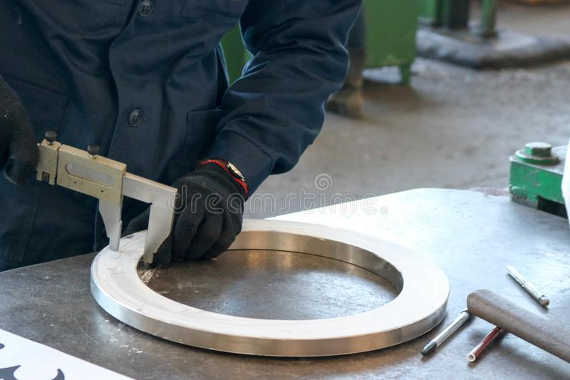 El trabajador mide el detalle, un anillo metálico brillante con un calibrador en una tabla verde de trabajo en la fábrica, el tal imagen de archivo