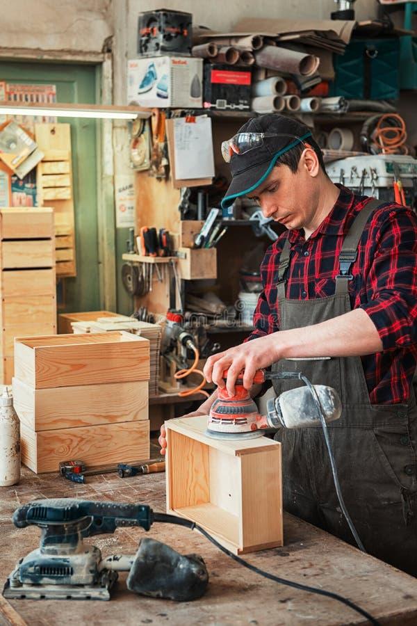 El trabajador muele la caja de madera imagen de archivo