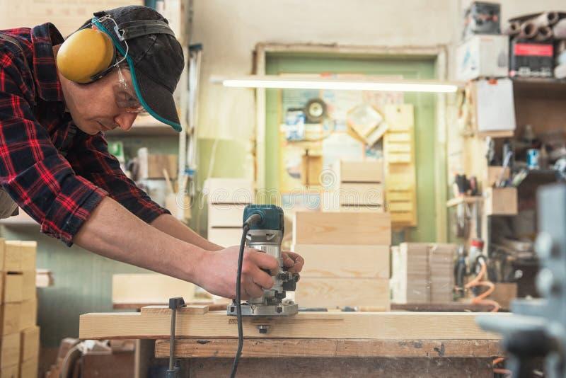 El trabajador muele la caja de madera fotos de archivo libres de regalías