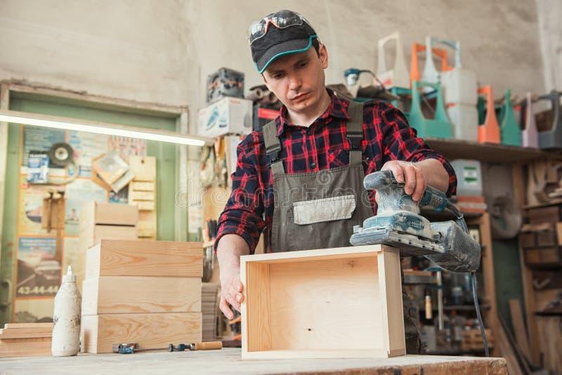 El trabajador muele la caja de madera imagen de archivo libre de regalías