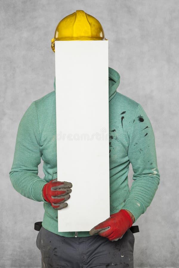 El trabajador oculta detrás de un espacio de publicidad vacío imagen de archivo