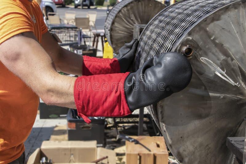 El trabajador para el asador caliente del chile del barril del torneado y se prepara para abrirlo los mits resistentes del horno  imagen de archivo libre de regalías