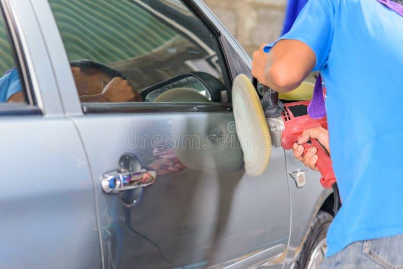 El trabajador pule el coche en coche foto de archivo libre de regalías