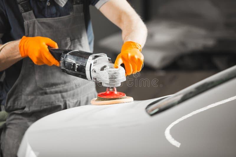 El trabajador pulió el coche blanco con el pulidor orbital en el taller de reparaciones auto, primer Detalle del veh?culo imagenes de archivo
