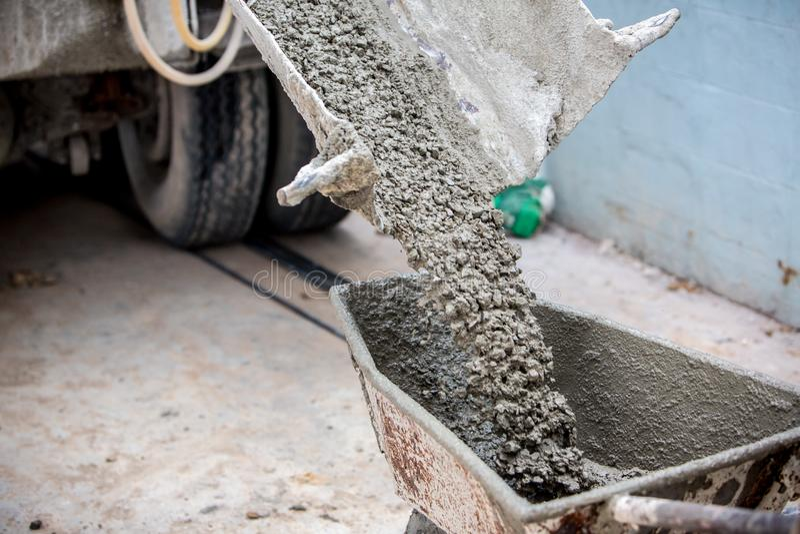 El trabajador que sostenía la carretilla para la ayuda que vertía Creta mezcló el camión de la amoladora del mortero del cemento foto de archivo