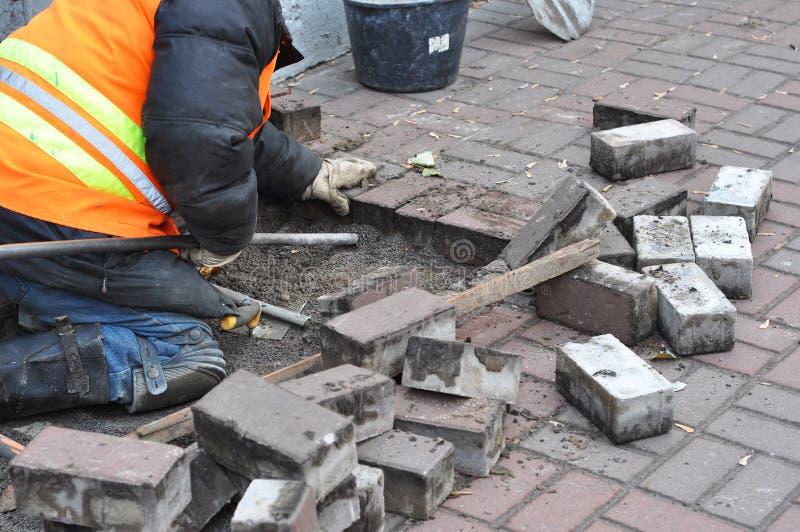 El trabajador quitan y los bloques de pavimentación concretos de la reparación imagen de archivo
