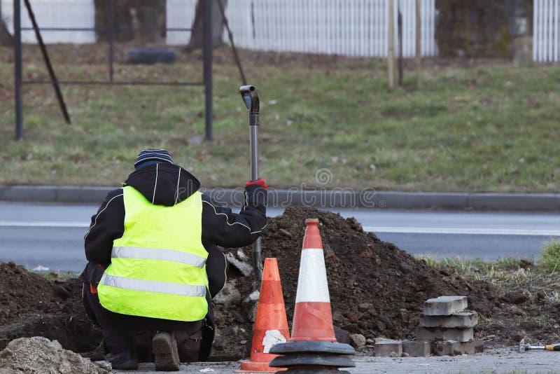 El trabajador repara el camino que dobla sobre el agujero cavado Un hombre con una pala examina la fosa Guardapolvos con los refl imágenes de archivo libres de regalías