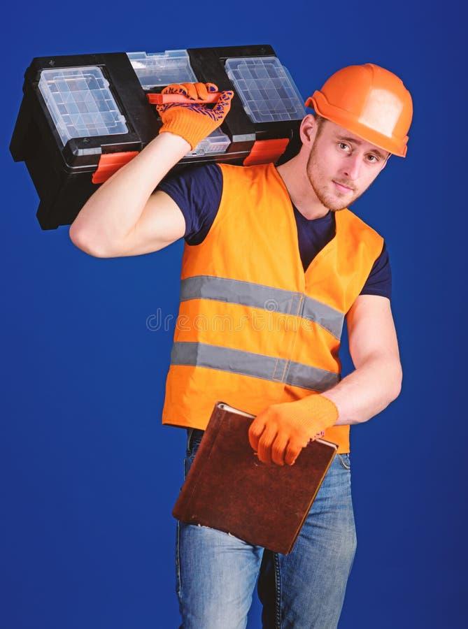 El trabajador, reparador, reparador, constructor en cara tranquila lleva la caja de herramientas en hombro, alista para trabajar  fotografía de archivo