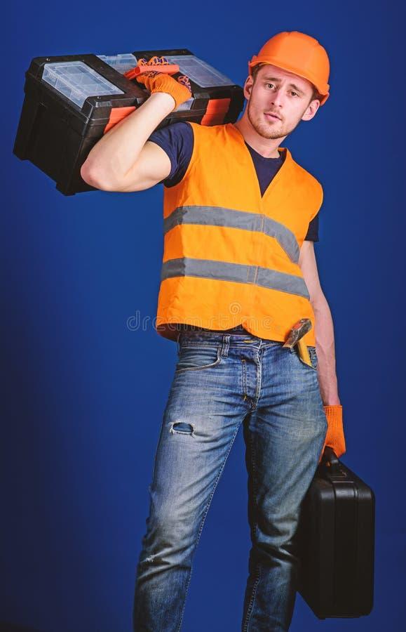 El trabajador, reparador, reparador, constructor en cara tranquila lleva la caja de herramientas en hombro, alista para trabajar  foto de archivo