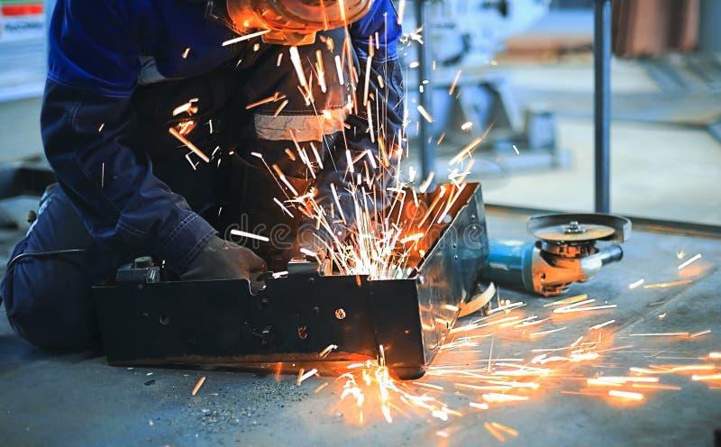 El trabajador se sienta en el piso concreto en la pieza del taller y de metal soldado con autógena Vuele las chispas brillantes imágenes de archivo libres de regalías