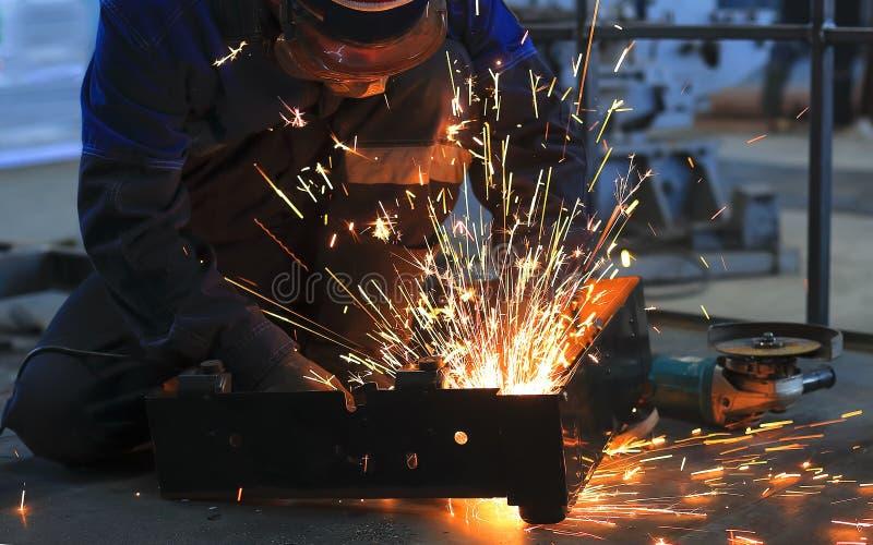 El trabajador se sienta en el piso concreto en la pieza del taller y de metal soldado con autógena Vuele las chispas brillantes fotos de archivo libres de regalías