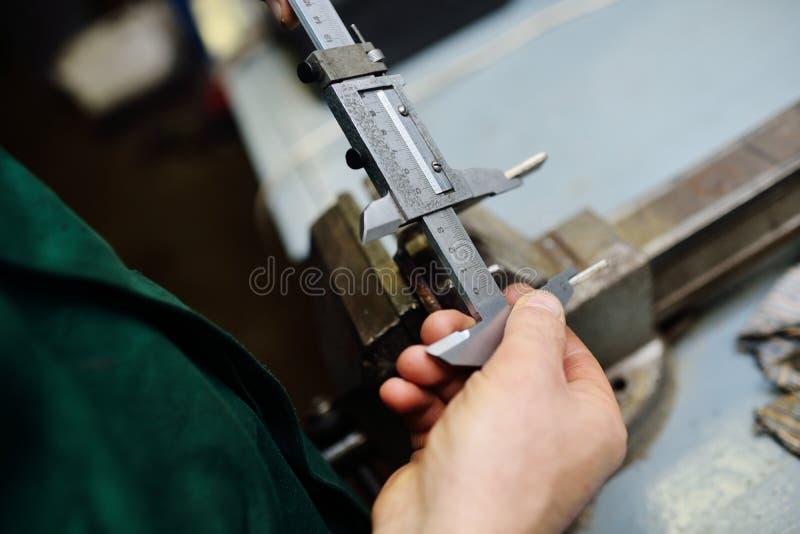 El trabajador sostiene un calibrador en sus manos y mide un detalle fotos de archivo libres de regalías