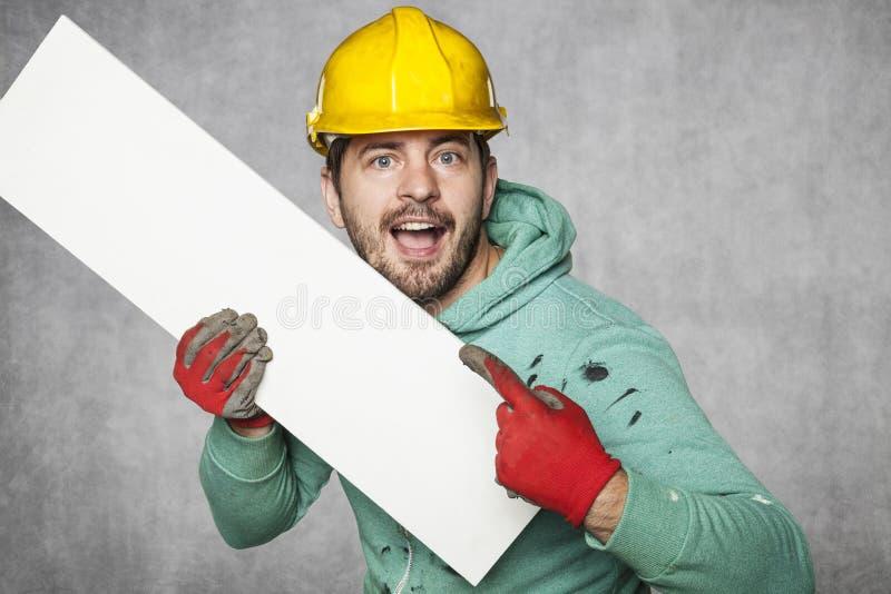 El trabajador sostiene una cartelera en blanco, un lugar para el ANUNCIO imagenes de archivo