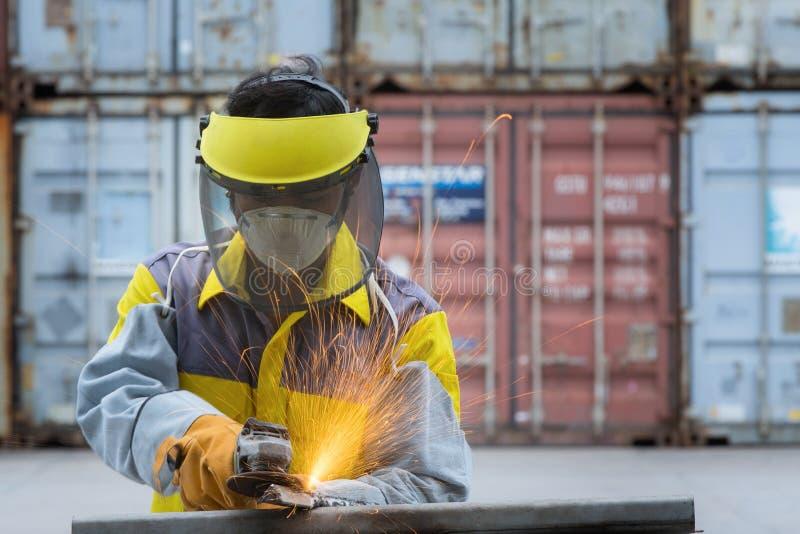 El trabajador toma el trabajo duro con el pulido eléctrico de la rueda foto de archivo libre de regalías