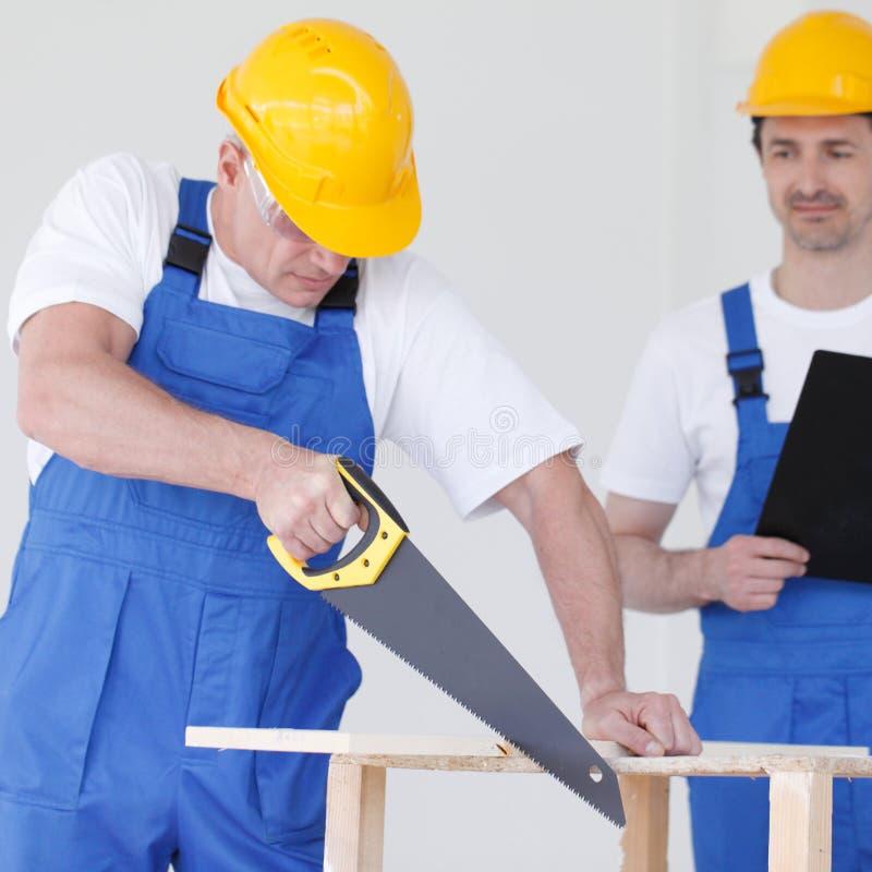 El trabajador trabaja con el handsaw imagen de archivo