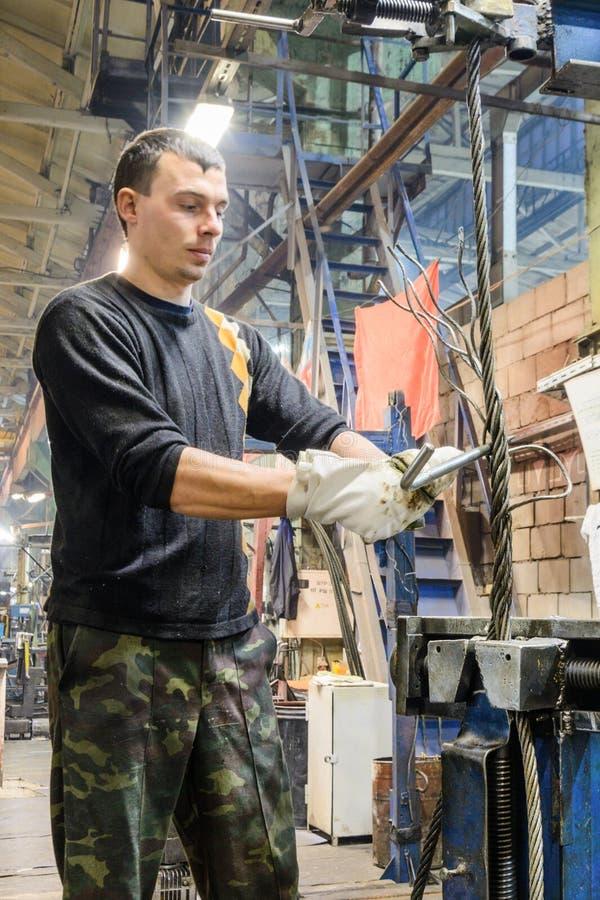 El trabajador trenza el extremo de las hondas de la cuerda de alambre de acero foto de archivo