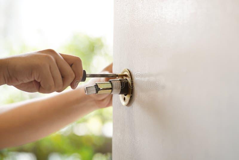 El trabajador utiliza un destornillador para quitar e instalar un pomo de puerta, enfoque selectivo, Conceptos de mantenimiento en foto de archivo libre de regalías