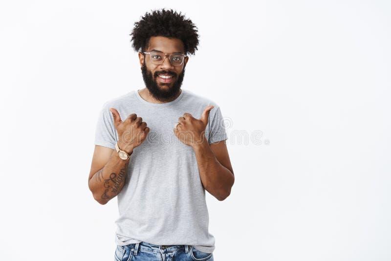 El trabajo agradable contin?a Retrato del novio afroamericano satisfecho apuesto de apoyo con los tatuajes, nariz perforada foto de archivo libre de regalías