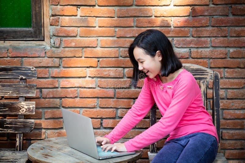 El trabajo asi?tico feliz de la ni?a o del estudiante, practicando surf Internet con el ordenador port?til en la tabla al aire li imagen de archivo