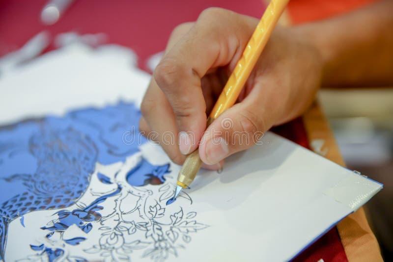 El trabajo de las manos del hombre está utilizando el cuchillo del arte, proceso de la mano que corta naga de las etiquetas del v foto de archivo libre de regalías