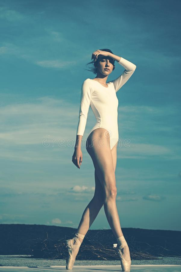 El trabajo de Pointe es trabajo duro Baile joven de la bailarina en el cielo azul Bailar?n de ballet lindo Muchacha bonita en des foto de archivo