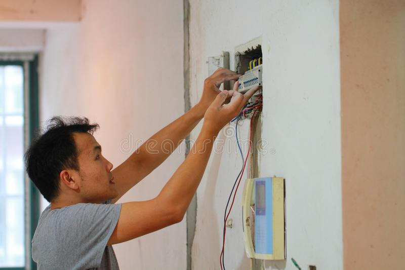 El trabajo de renovación eléctrico, hombre instala el equipo eléctrico industrial imagenes de archivo