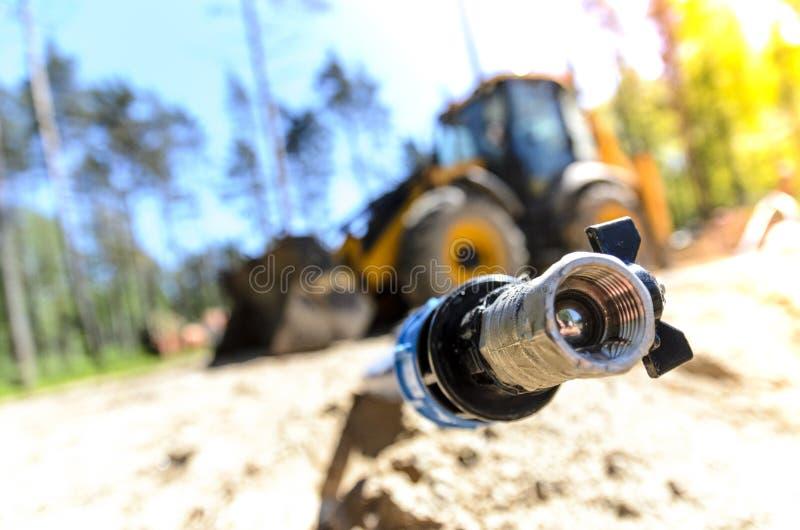 El trabajo de un tractor de dos ruedas grande al poner el abastecimiento de agua para el abastecimiento de agua de propiedades pr fotografía de archivo