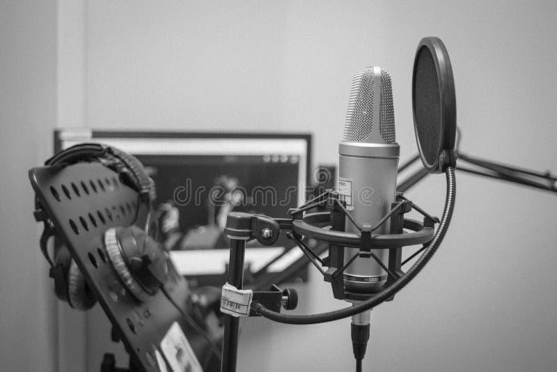El trabajo del anunciador y del actor de la voz que actúan y que doblan delante del micrófono fotografía de archivo libre de regalías