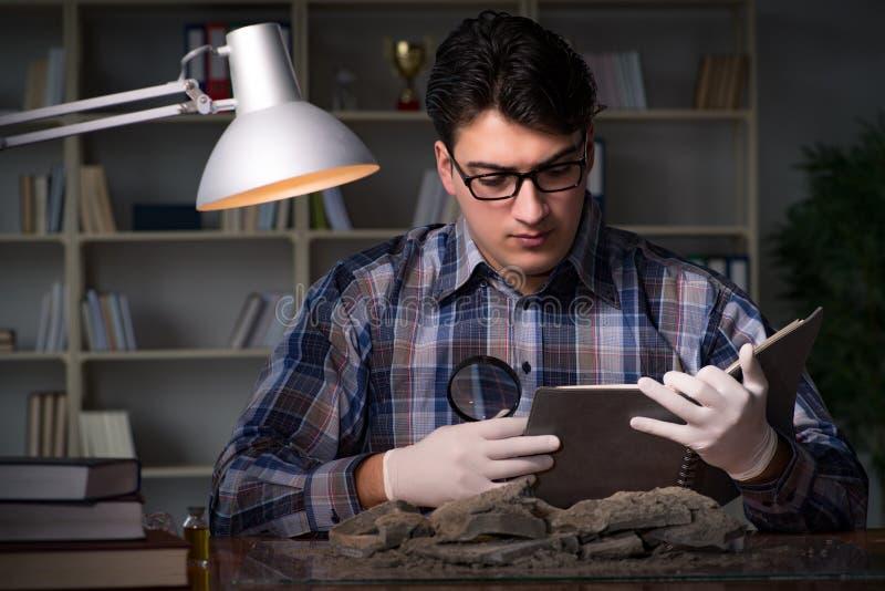 El trabajo del arqueólogo de última hora en oficina imágenes de archivo libres de regalías