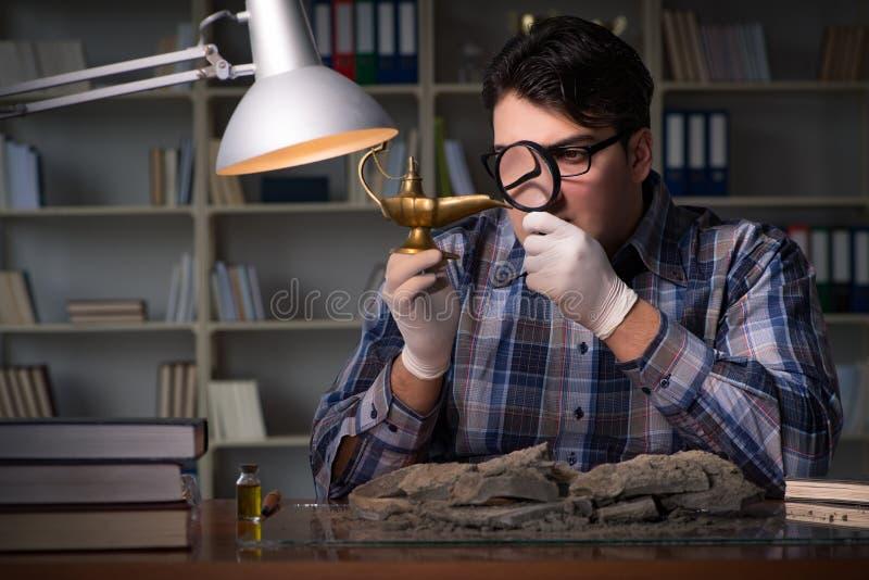 El trabajo del arqueólogo de última hora en oficina foto de archivo libre de regalías