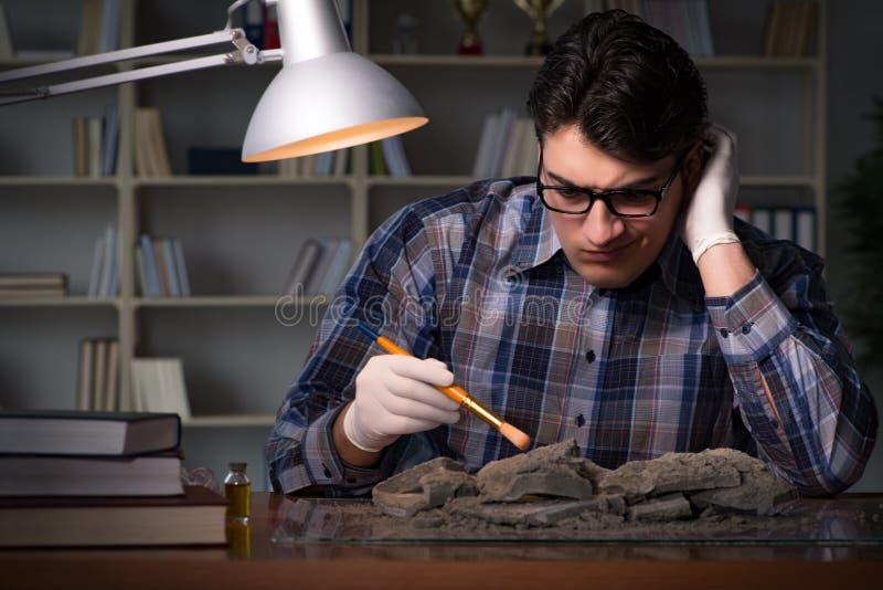 El trabajo del arqueólogo de última hora en oficina fotos de archivo libres de regalías