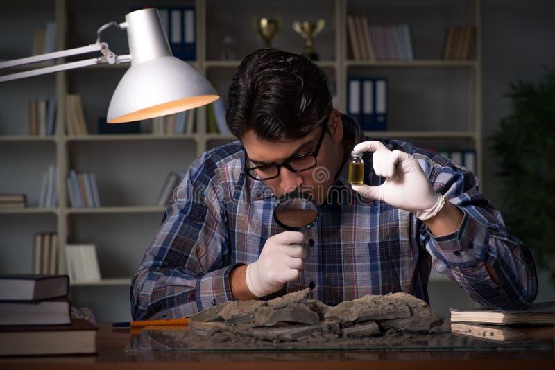 El trabajo del arqueólogo de última hora en oficina foto de archivo
