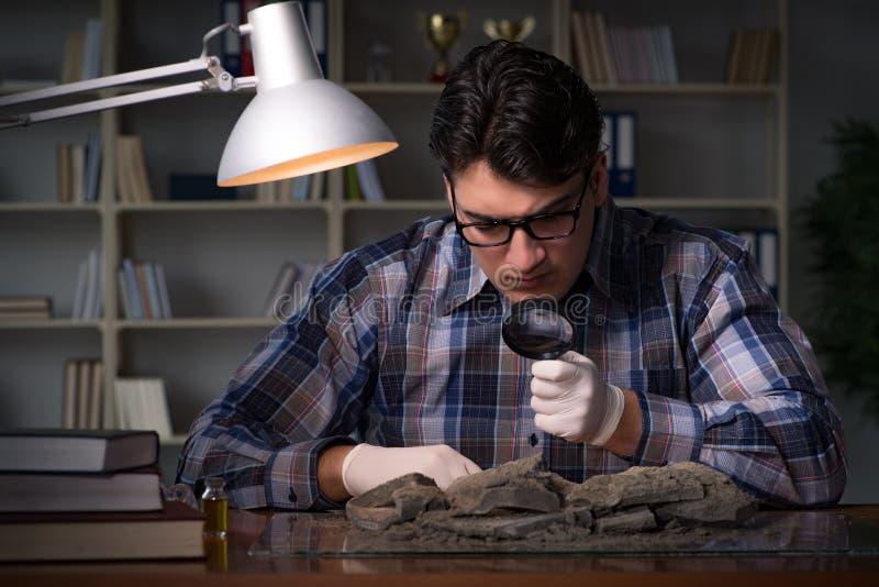 El trabajo del arqueólogo de última hora en oficina fotos de archivo