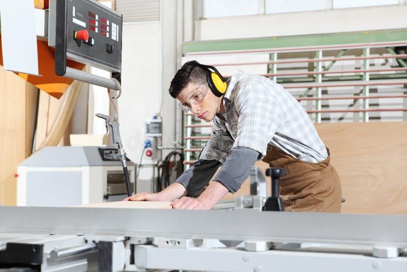 El trabajo del hombre del carpintero en la carpinter?a, cort? a un tablero de madera con la m?quina circular de la sierra, proteg fotografía de archivo