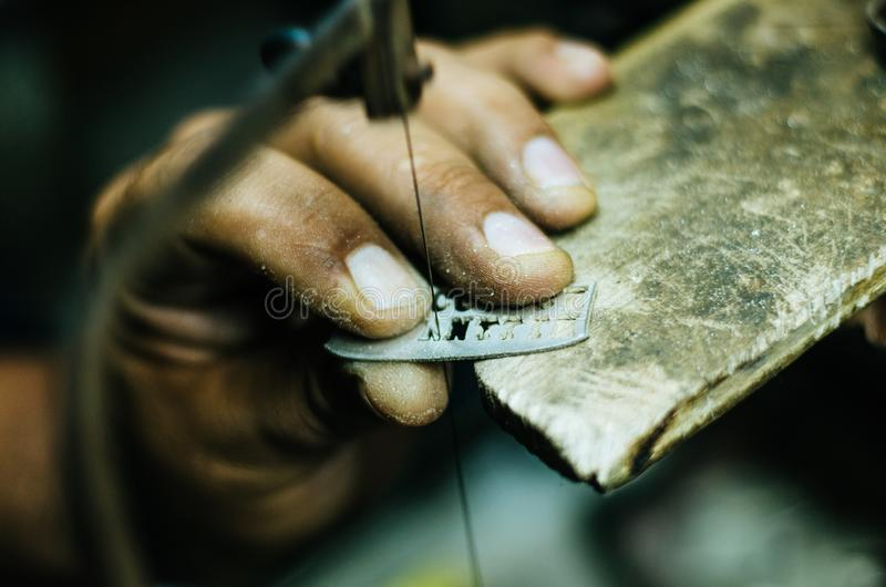El trabajo del orfebre de las manos del hombre sobre un pedazo de plata con un metal consideró en la tabla de trabajo, cierre par fotografía de archivo libre de regalías