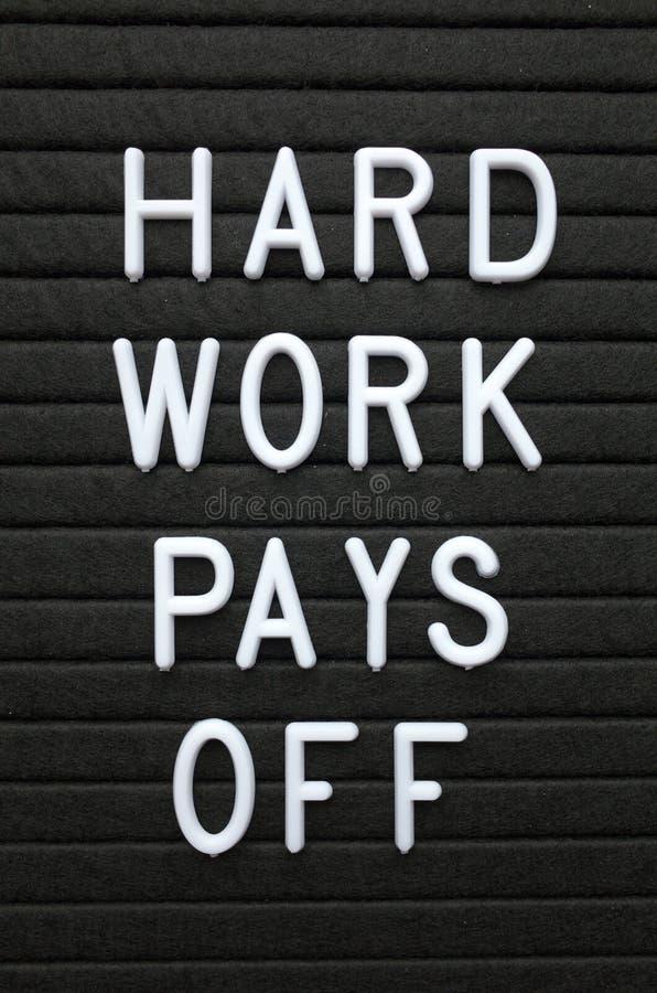 El trabajo duro de la frase paga apagado en las letras blancas en un tablón de anuncios fotografía de archivo
