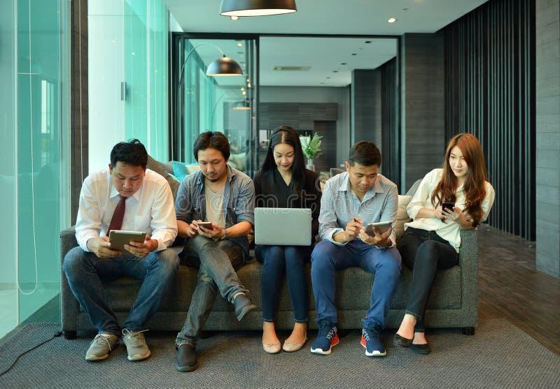 El trabajo en equipo de hombres de negocios asiáticos no está interesado en cada uno más allá del horizonte imágenes de archivo libres de regalías